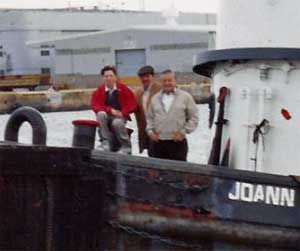 The three Joes on the bow of a tugboat